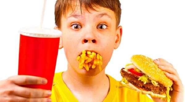 Мальчик ест фаст-фуд