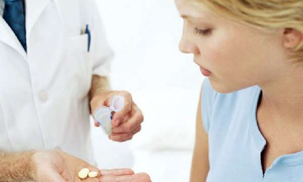 Врач дает девушке таблетки